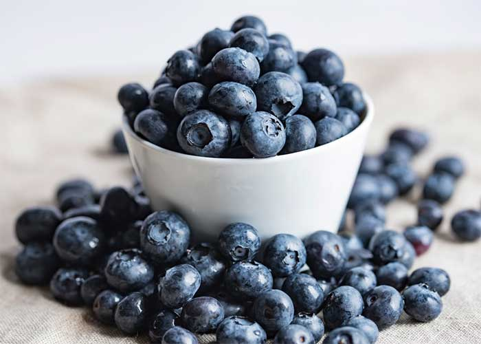 blueberries in a white bowl on a wooden table with loose blueberries scattered around the bowl