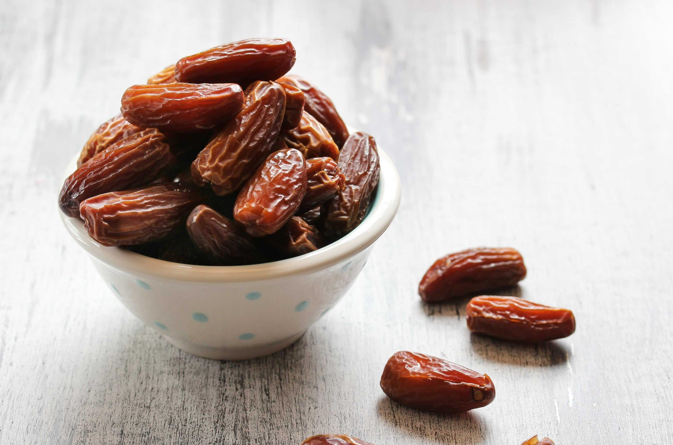 Photo of a white ceramic bowl over filled with dates spilling onto a white washed wooden surface.