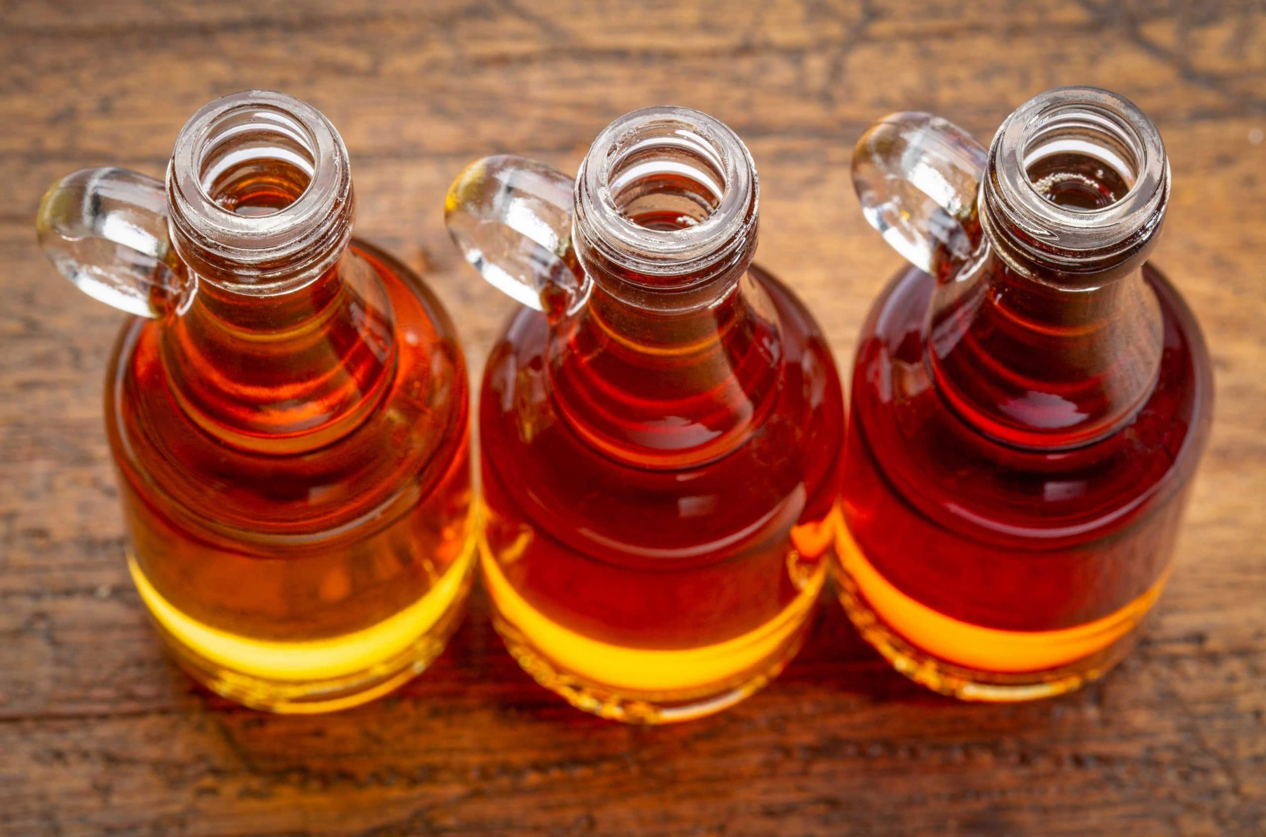 Photo of three small glass jugs of maple syrup in a row on a wooden surface.