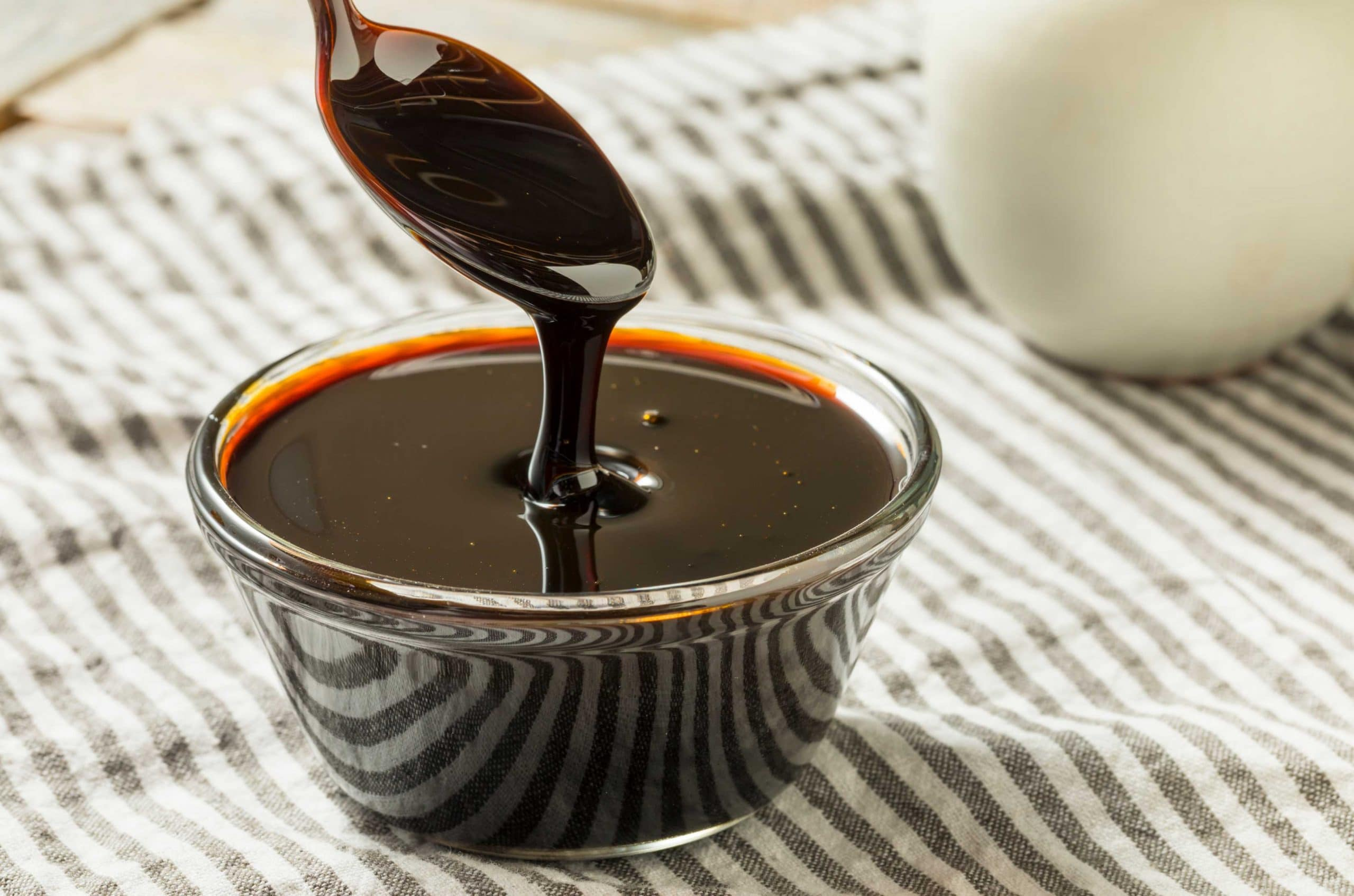 On a gray and white striped tablecloth sits a small glass bowl full of black strap molasses with a spoon that has just been dipped in the syrup and raised out of the bowl.
