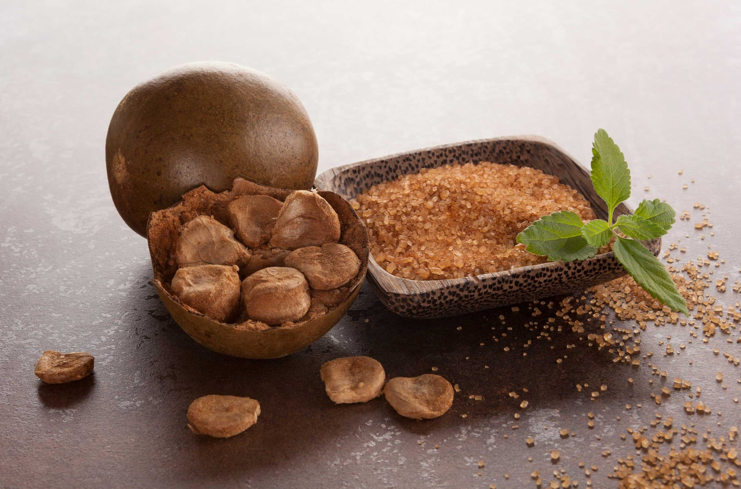 Photo of a wooden bowl of granulated monk fruit with a sprig of the plant on the edge of the bowl. The bowl is next to pieces of dried monk fruit and behind that is a piece of the whole monk fruit. They are all on a brown flat surface.