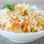 White ceramic bowl on gray linen tablecloth with coleslaw in it garnished with parsley