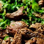 pile of cooked sliced skirt steak with fresh chopped cilantro on top